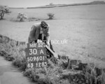SD960130A, Man marking Ordnance Survey minor control revision point with an arrow in 1950s