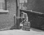 SD960297A, Man marking Ordnance Survey minor control revision point with an arrow in 1950s