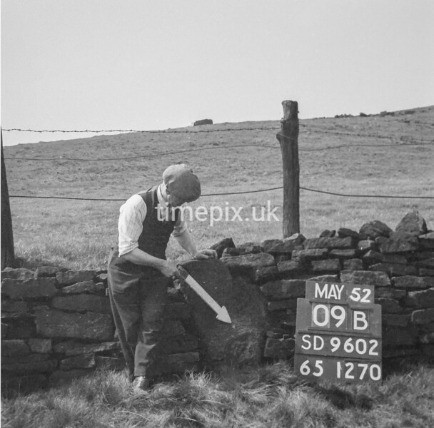 SD960209B, Man marking Ordnance Survey minor control revision point with an arrow in 1950s