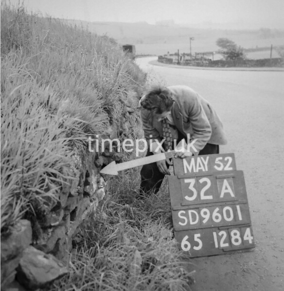 SD960132A, Man marking Ordnance Survey minor control revision point with an arrow in 1950s