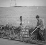 SD960131A, Man marking Ordnance Survey minor control revision point with an arrow in 1950s