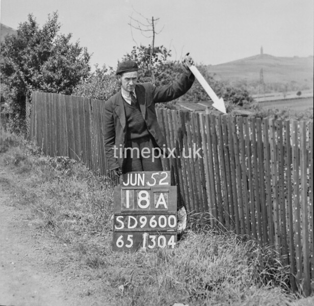 SD960018A, Man marking Ordnance Survey minor control revision point with an arrow in 1950s