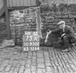 SD950273A, Man marking Ordnance Survey minor control revision point with an arrow in 1950s