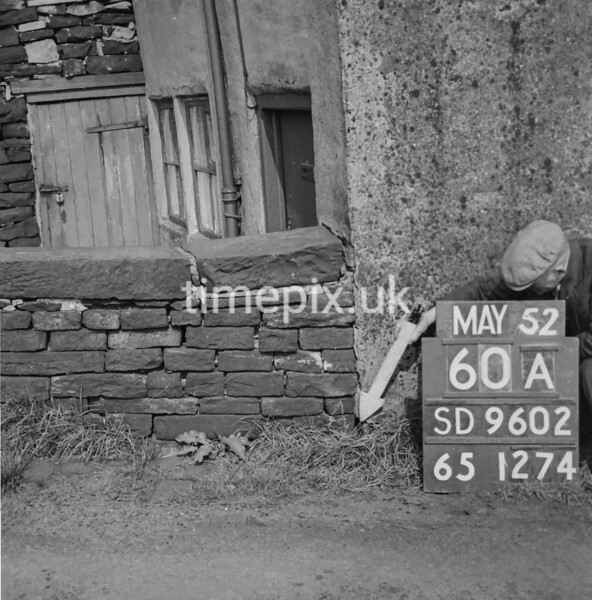 SD960260A, Man marking Ordnance Survey minor control revision point with an arrow in 1950s