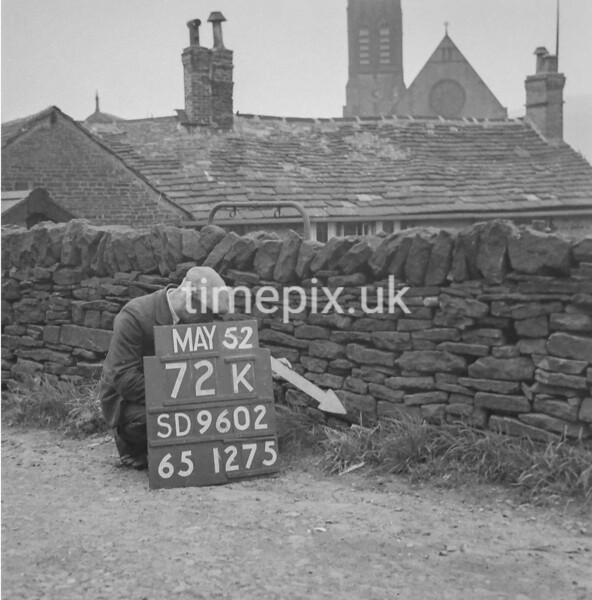 SD960272K, Man marking Ordnance Survey minor control revision point with an arrow in 1950s