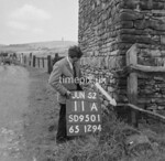 SD950111A, Man marking Ordnance Survey minor control revision point with an arrow in 1950s