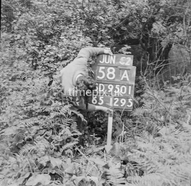 SD950158A, Man marking Ordnance Survey minor control revision point with an arrow in 1950s