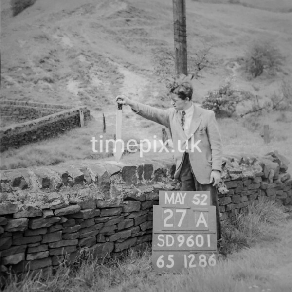 SD960127A, Man marking Ordnance Survey minor control revision point with an arrow in 1950s