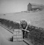 SD960168A, Man marking Ordnance Survey minor control revision point with an arrow in 1950s