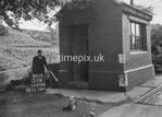 SD970051A, Man marking Ordnance Survey minor control revision point with an arrow in 1950s