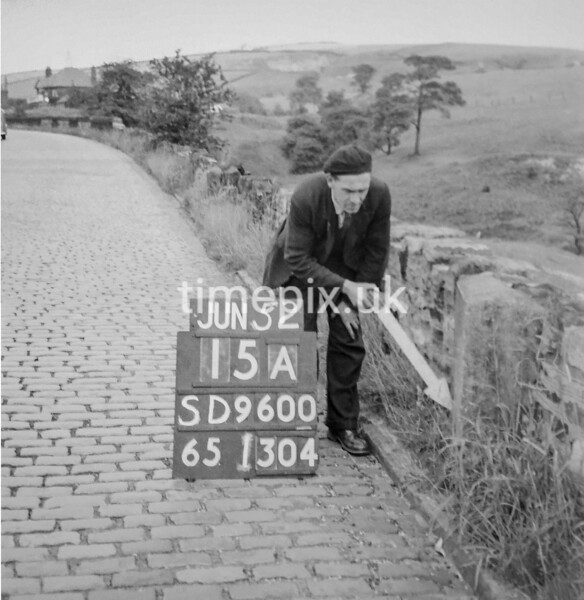 SD960015A, Man marking Ordnance Survey minor control revision point with an arrow in 1950s