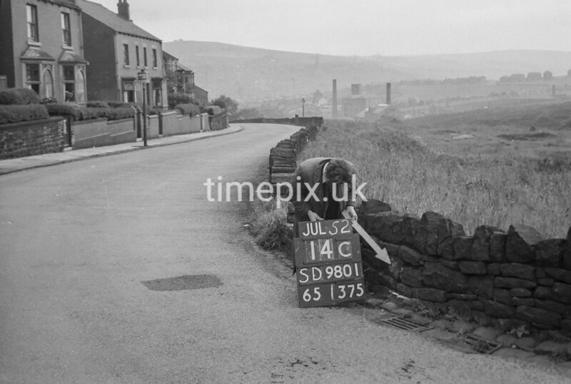 SD980114C, Man marking Ordnance Survey minor control revision point with an arrow in 1950s