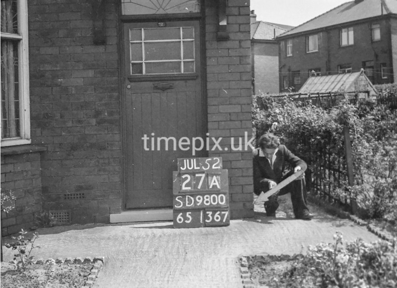SD980027A, Man marking Ordnance Survey minor control revision point with an arrow in 1950s