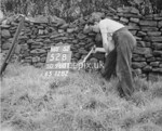 SD960152B, Man marking Ordnance Survey minor control revision point with an arrow in 1950s