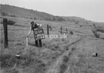 SD970015A, Man marking Ordnance Survey minor control revision point with an arrow in 1950s