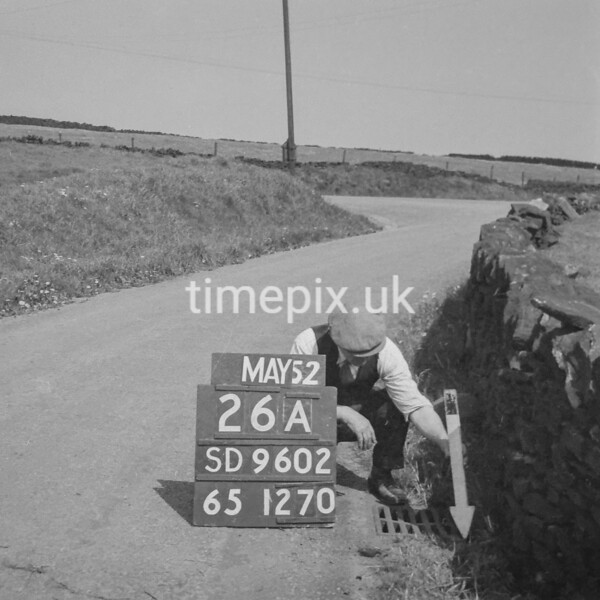 SD960226A, Man marking Ordnance Survey minor control revision point with an arrow in 1950s