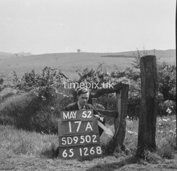 SD950217A, Man marking Ordnance Survey minor control revision point with an arrow in 1950s