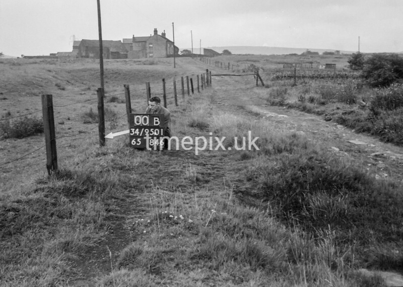 SD950100B, Man marking Ordnance Survey minor control revision point with an arrow in 1950s