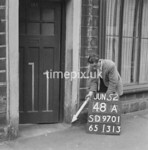 SD970148A, Man marking Ordnance Survey minor control revision point with an arrow in 1950s