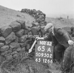 SD950265A, Man marking Ordnance Survey minor control revision point with an arrow in 1950s