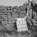 SD960227A, Man marking Ordnance Survey minor control revision point with an arrow in 1950s