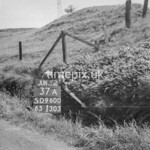 SD960037A, Man marking Ordnance Survey minor control revision point with an arrow in 1950s