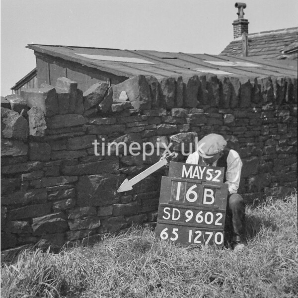 SD960216B, Man marking Ordnance Survey minor control revision point with an arrow in 1950s