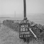 SD960050B, Man marking Ordnance Survey minor control revision point with an arrow in 1950s