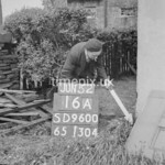 SD960016A, Man marking Ordnance Survey minor control revision point with an arrow in 1950s