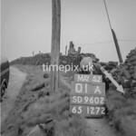 SD960201A, Man marking Ordnance Survey minor control revision point with an arrow in 1950s