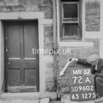 SD960272A, Man marking Ordnance Survey minor control revision point with an arrow in 1950s
