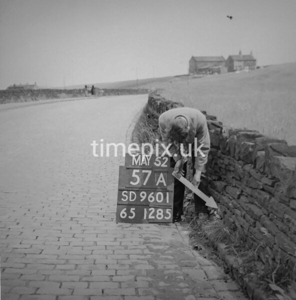 SD960157A, Man marking Ordnance Survey minor control revision point with an arrow in 1950s