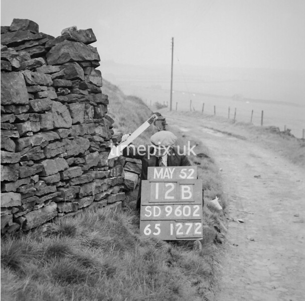 SD960212B, Man marking Ordnance Survey minor control revision point with an arrow in 1950s