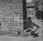 SD960296A, Man marking Ordnance Survey minor control revision point with an arrow in 1950s