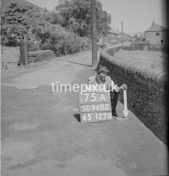 SD960275A, Man marking Ordnance Survey minor control revision point with an arrow in 1950s