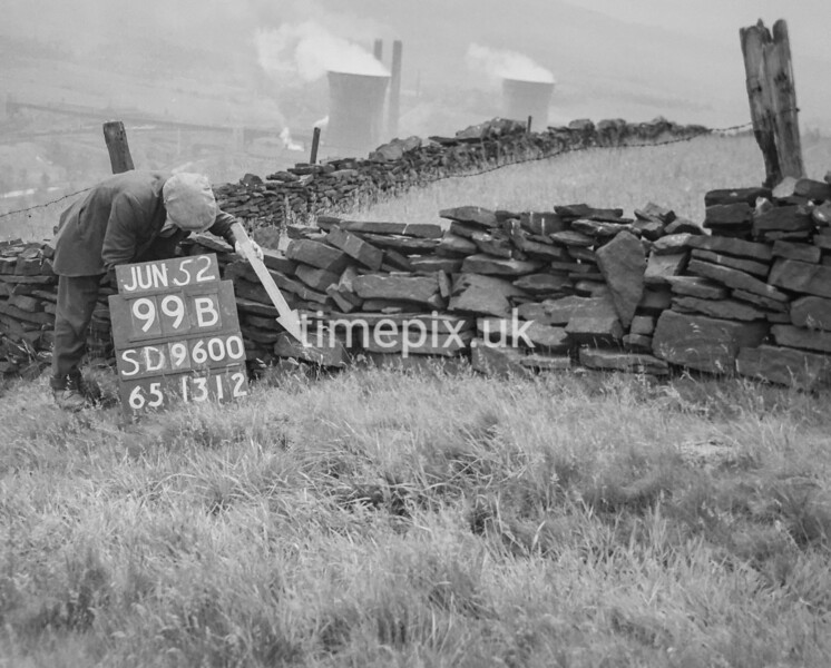 SD960099B, Man marking Ordnance Survey minor control revision point with an arrow in 1950s