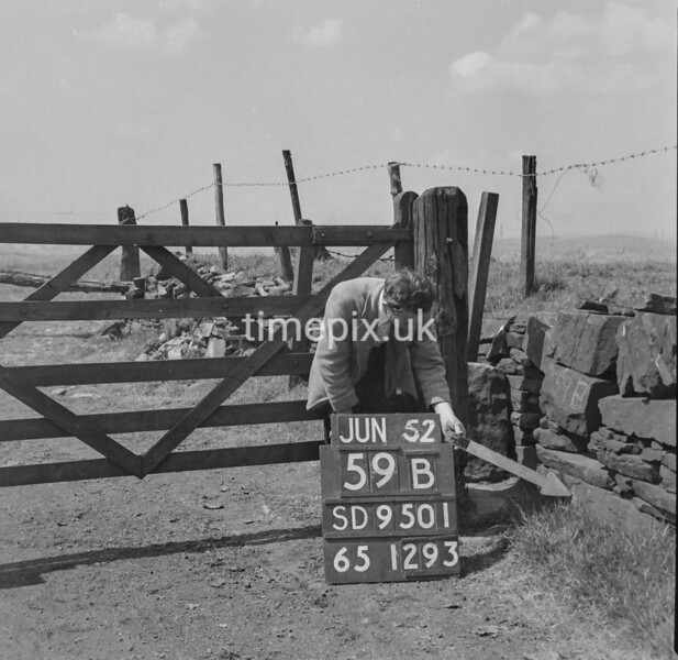 SD950159B, Man marking Ordnance Survey minor control revision point with an arrow in 1950s