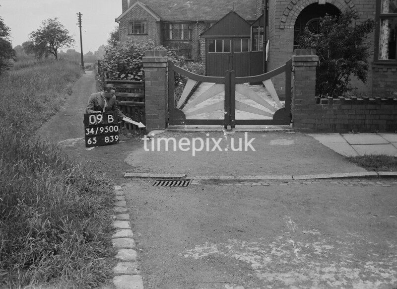 SD950009B, Man marking Ordnance Survey minor control revision point with an arrow in 1950s
