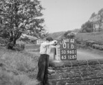 SD960101B, Man marking Ordnance Survey minor control revision point with an arrow in 1950s