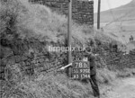SD970278B, Man marking Ordnance Survey minor control revision point with an arrow in 1950s