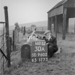 SD960230A, Man marking Ordnance Survey minor control revision point with an arrow in 1950s