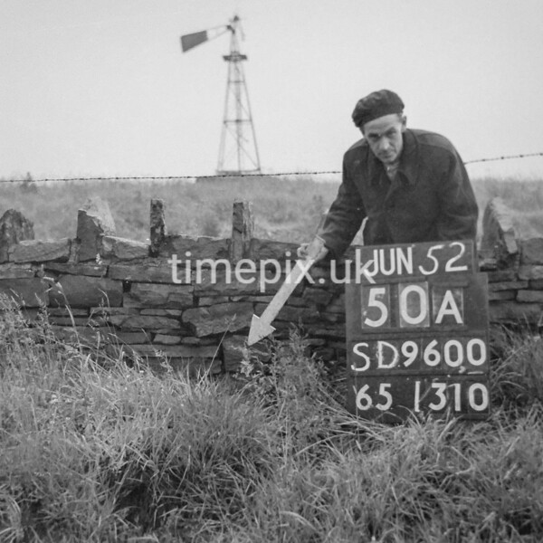 SD960050A, Man marking Ordnance Survey minor control revision point with an arrow in 1950s