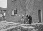 SD980024A, Man marking Ordnance Survey minor control revision point with an arrow in 1950s
