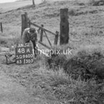 SD960048A, Man marking Ordnance Survey minor control revision point with an arrow in 1950s