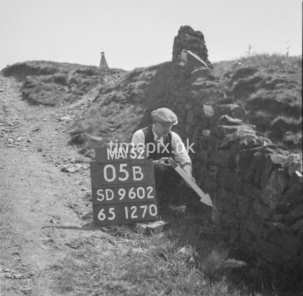 SD960205B, Man marking Ordnance Survey minor control revision point with an arrow in 1950s