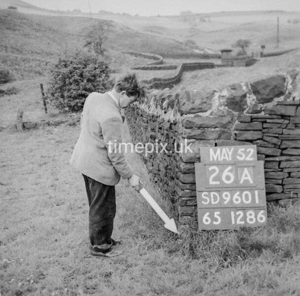 SD960126A, Man marking Ordnance Survey minor control revision point with an arrow in 1950s