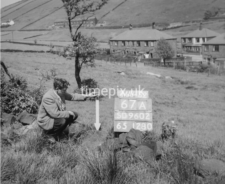 SD960267A, Man marking Ordnance Survey minor control revision point with an arrow in 1950s