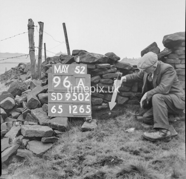 SD950296A, Man marking Ordnance Survey minor control revision point with an arrow in 1950s