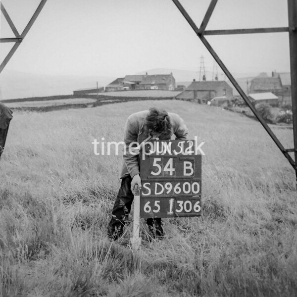SD960054B, Man marking Ordnance Survey minor control revision point with an arrow in 1950s