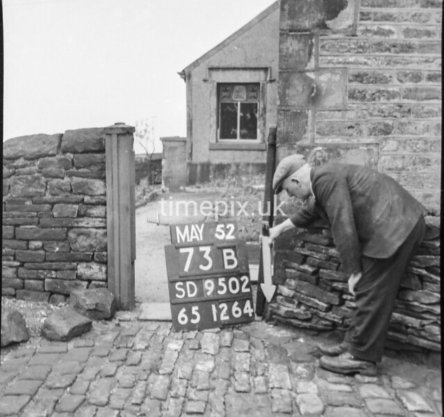 SD950273B, Man marking Ordnance Survey minor control revision point with an arrow in 1950s